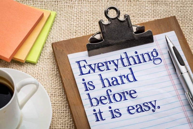 Everything is hard before it is easy - motivational slogan on a clipboard with a cup of coffee