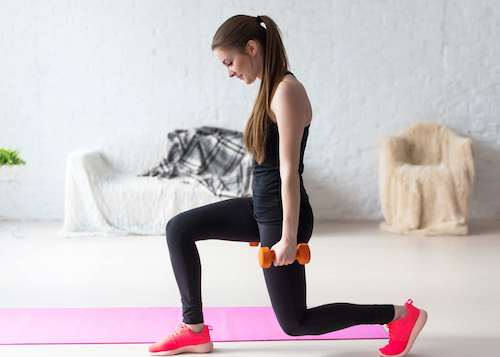 Athletic woman warming up doing weighted lunges with dumbbells workout exercise for butt legs at home healthy lifestyle sport bodybuilding concept.